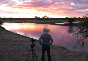 Gun Ringer - a man looking off into the sunset with camera equipment next to him